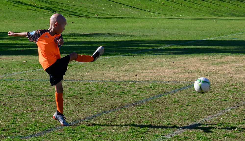 boy playing soccer showing hip motion